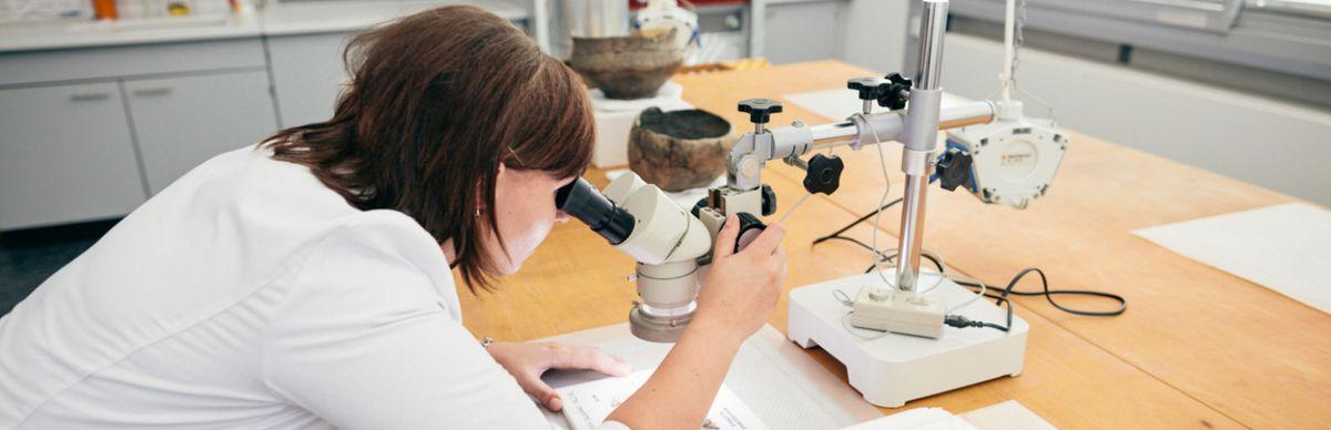 """Eine Wissenschaftlerin schaut durch ein Mikroskop im Laborkomplex """"Restaurierung und Konservierung"""""""