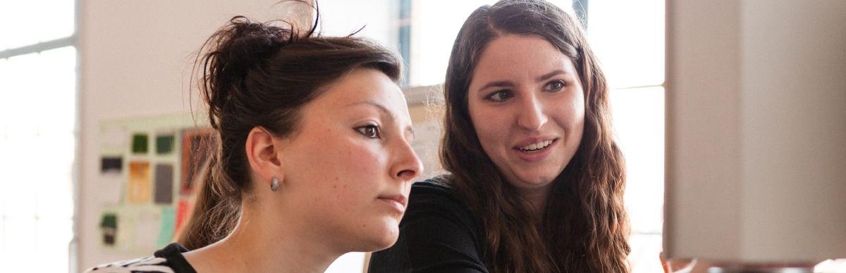 Zwei junge Frauen, die auf einen Bildschirm gucken