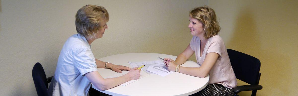 Zwei Frauen beraten sich an einem Tisch