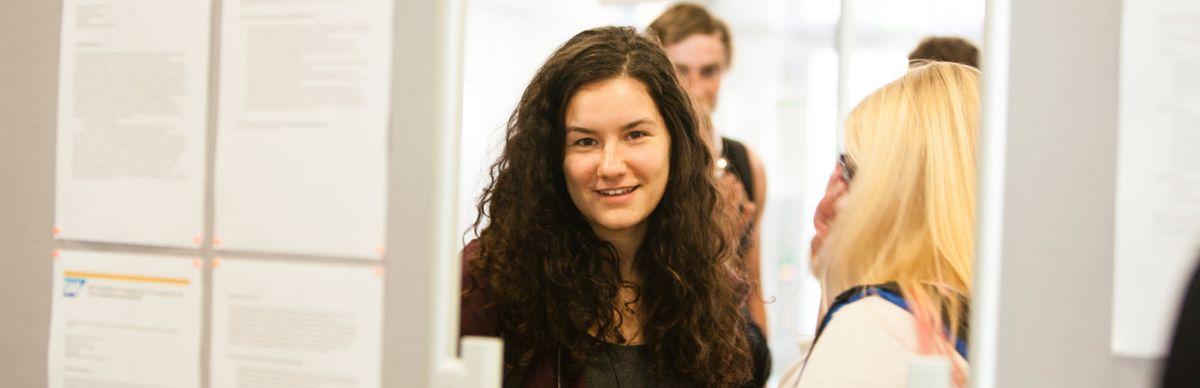 Studentin, im Vordergrund Pinnwand mit Stellenangeboten