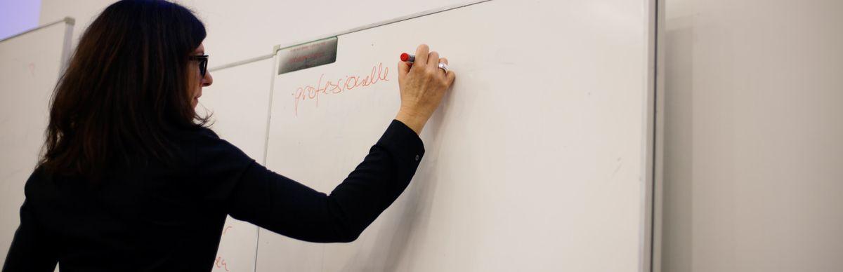 Professorin schreibt an einer Tafel