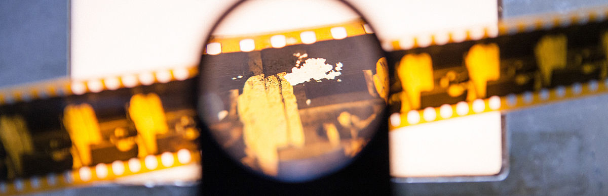 """Historische Filmrolle unter einer Lupe im Laborkomplex """"Audiovisuelles und fotografisches Kulturgut"""""""