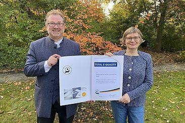 Der Präsident Prof. Dr.-Ing. Carsten Busch und die Frauenbeauftragte Dr Sünne Andresen halten die Urkunde