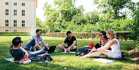 Group of students sitting in a meadow on the Campus Treskowallee