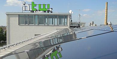 Solarzellen auf einem Dach auf dem Campus Wilhelminenhof, im Hintergrund das Hochschullogo