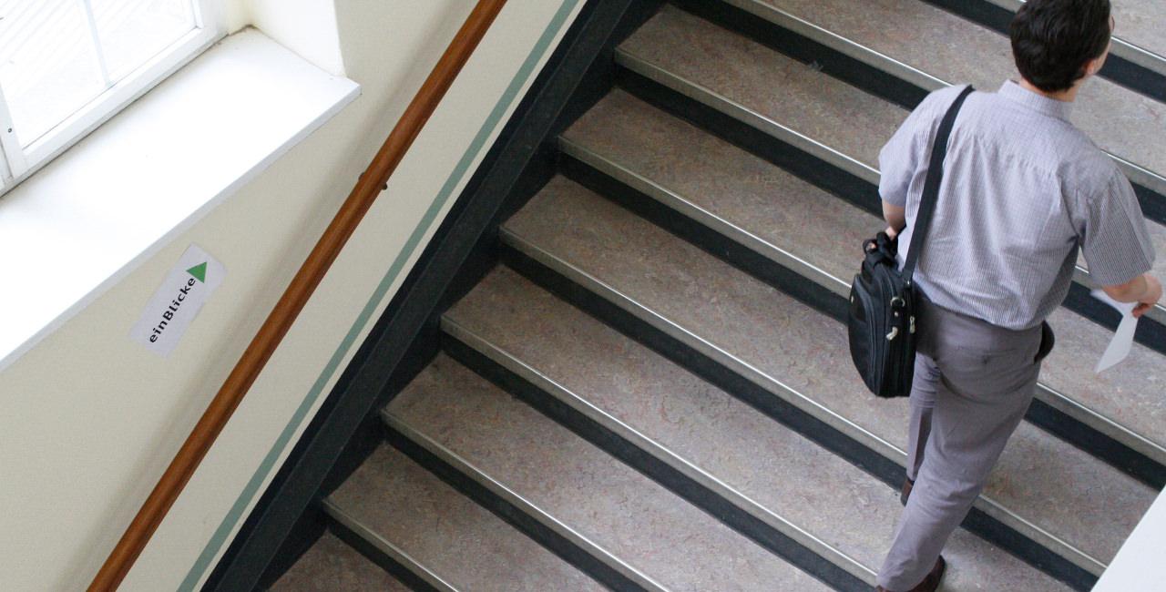 Mann mit Labtoptasche steigt eine Treppe hoch