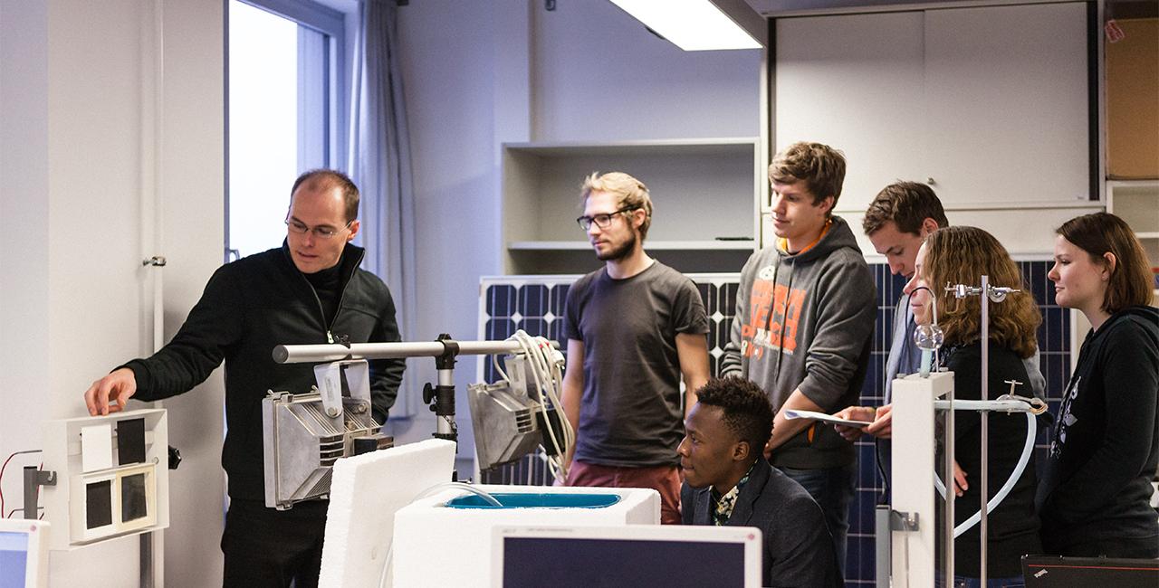 Laboringenieur erklärt Studierenden etwas im Labor