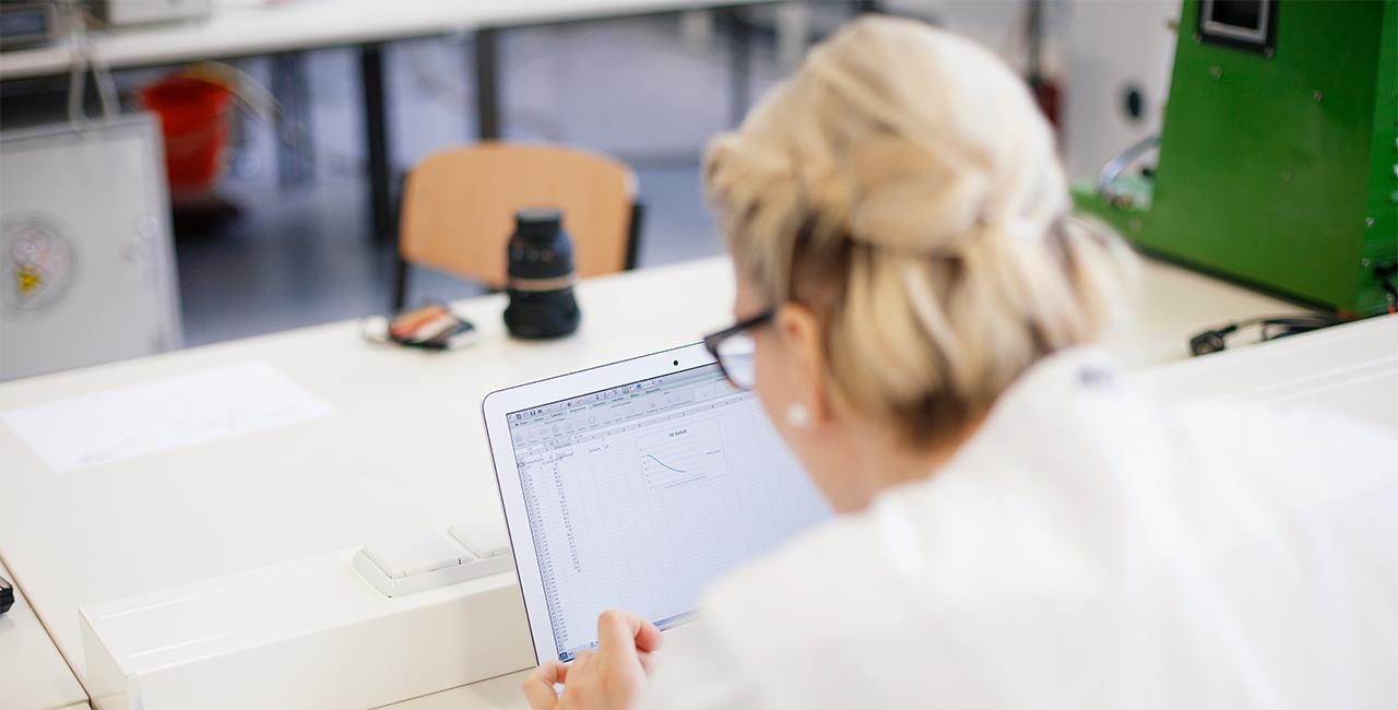 Wissenschaftliche Mitarbeiterin im Laborkittel am Laptop