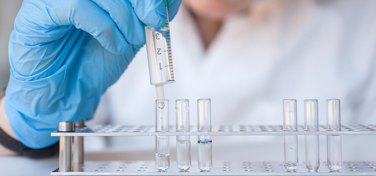 Forscherin füllt Flüssigkeit in Reagenzglas