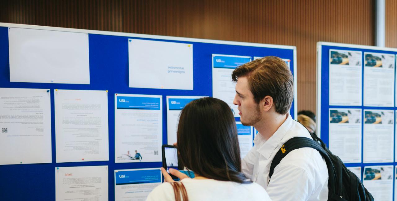 Zwei Studierende stehen vor einer Pinnwand mit Stellenangeboten